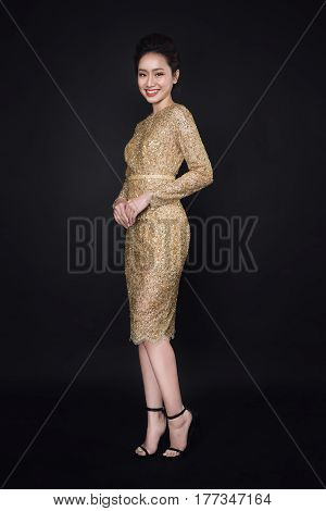 Full length portrait of happy attractive young woman posing cocktail dresses over black background