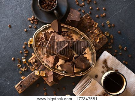 Pieces of bittersweet dark chocolate spread out on a dark background and a mug of coffee
