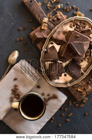 Pieces of bittersweet dark chocolate spread out on a dark background and a mug of coffee Americano