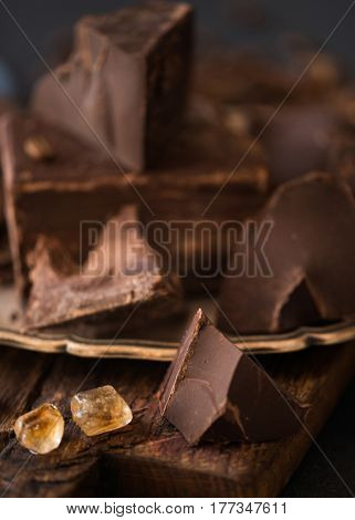 Pieces of bittersweet dark chocolate spread out on a wooden background, macro view