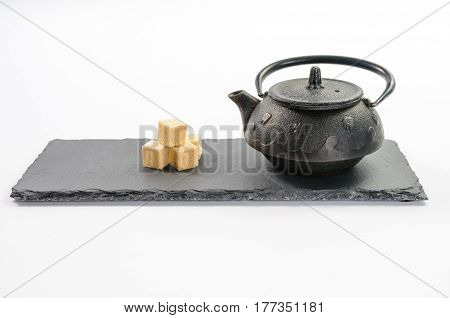 Cast-iron black teapot and four cane sugar cubes beside on rectangular shale plate on white background