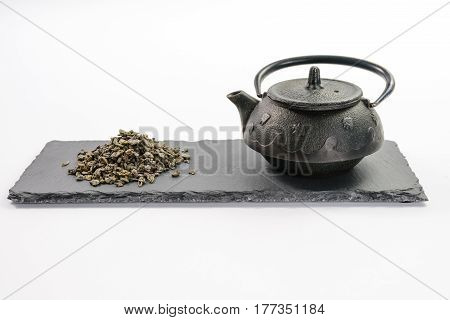 Cast-iron black teapot and handful of leaf green tea on rectangular shale plate on white background