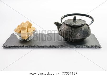 Cast-iron black teapot and several cane sugar cubes in glass bowl on rectangular shale plate on white background