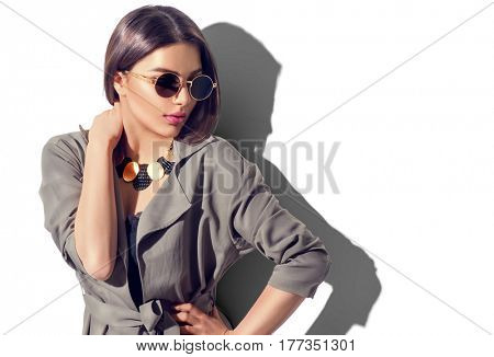 Beauty Fashion brunette model girl wearing stylish coat and sunglasses. Sexy woman portrait with perfect makeup, trendy accessories and fashion wear. Beauty trends. Isolated on white. Fashion blogger
