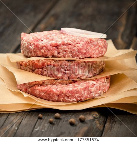 Close up raw ground beef meat cutlets on wooden table