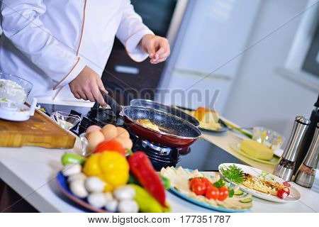 Man's hand holding an egg. White chicken egg. Chef starts preparing omelet. Only clean products.