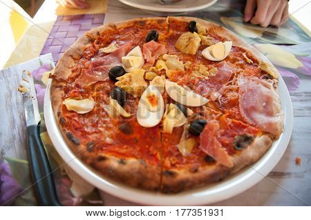 Italian pizza with ham, artichokes, eggs and cheese served on the plate