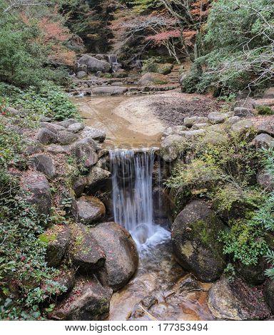 Waterfall with autumn leaves in Momijidani Park in Miyajima, Japan