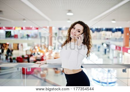 Young Curly Model Girl Speaking On Phone At Large Shopping Center Near Glass Railings.