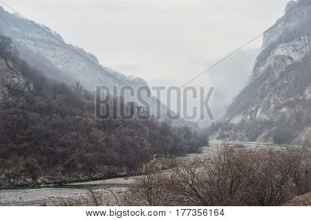 The bed of a mountain river flowing in a misty gorge with a prospect of fading into the mist fog