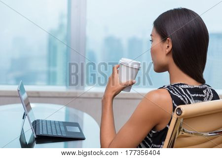 Businesswoman taking a coffee break at work looking out the window thinking about career opportunities or life goals. Asian business woman drinking hot drink in office.
