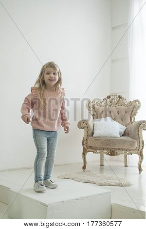 Little modern princess in jeans near her throne, white background