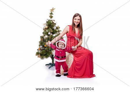 Cute little Santa posing at studio near New Year tree with mom