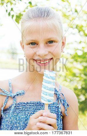 Portrait of 7 years old kid. Little girl eating tasty white blue ice cream
