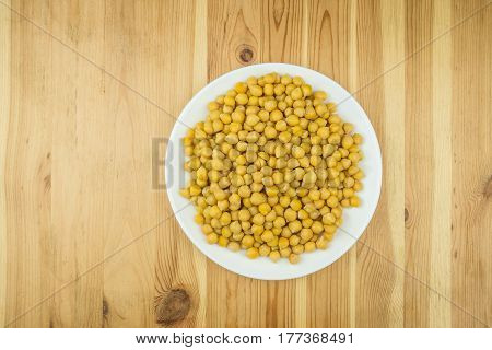Bowl of chickpeas on wood table. Cooked gram-chick peas on a plate photographed from the top