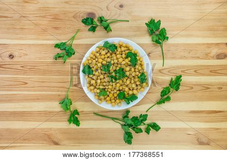 Cheakpea and parsley top view. Bowl of cooked gram-chick peas seasoned with parsley as flat lay on wood table