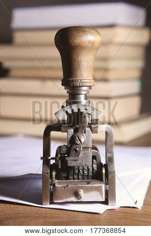 Vintage date stamp. Industrial office stamp. Old numbering machine on table with documents