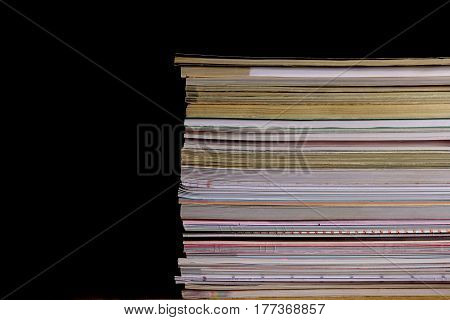 Pile of  journals in front of  black background. Texture of pile of magazine in black.