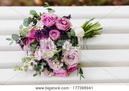 A purpule wedding bouquet of flowers rests on a white bench
