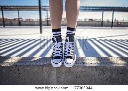 Details Of Woman Legs Standing On Concrete Ledge In Her Classic Sneakers