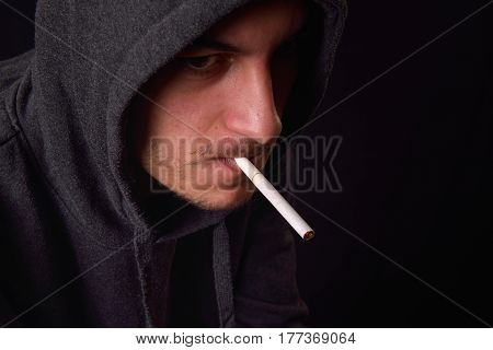Pensive And Depressed Teenager In A Black Hooded Sweatshirt Smoking A Cigarette On A Dark Background