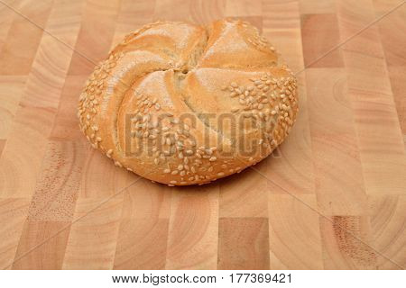 Freshly baked whole grain round sandwich bun sprinkled with sesame seeds on wooden table background. Whole grain baguette
