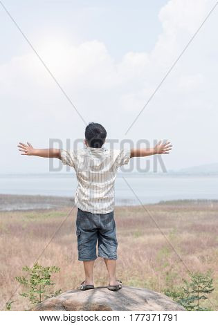Freedom and happiness child at dam. He is enjoying serene water in dam during travel holidays vacation outdoors