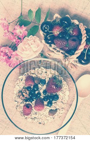 A bowl with hole grain flakes berries nuts and rose on sackcloth beige background. Healthy breakfast. Top view. Vintage toned
