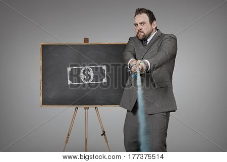 Businessman pulling rope with blackboard - studio shot