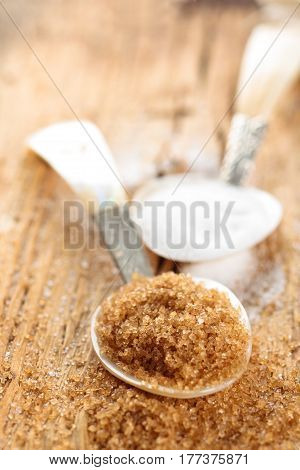 White and brown sugar in spoon on rustic wooden table.