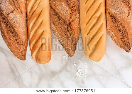 Loaves of rye and wheat bread with traces of flour, shot from above on a white marble table with a place for text