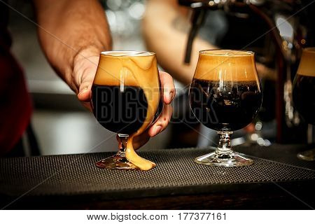 Glass of dark beer with froth in bar
