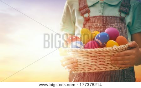 Cute little child hunts for Easter eggs in the rays of the setting sun.