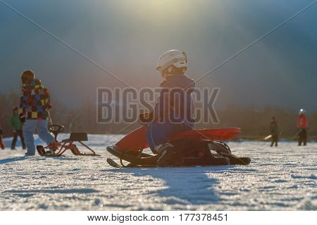child comes down from the mountain riding a red sled in winter