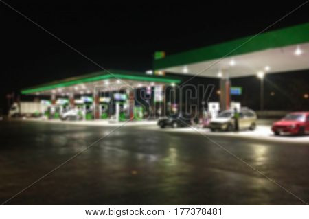 Blurred image of gas station at night.Abstract blur petrol station background with copy space.