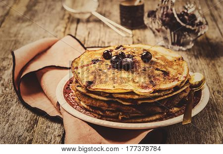 Stack of homemade freshly baked pancakes crepes with black currant berries on a rustic vintage wooden background. Healthy breakfast. Selective focus. Vintage toned