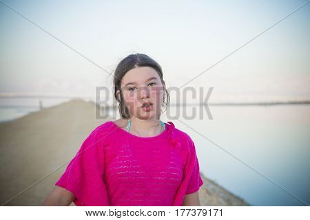 Sad and confused teenager girl in pink t-shirt on road to horizon background
