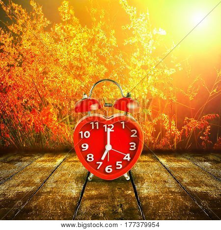 Red clock mark on 7 o'clock put on wooden tabletop with abstract blurred on fresh green nature background and bokeh of sunlight ray, Time to relax concept.