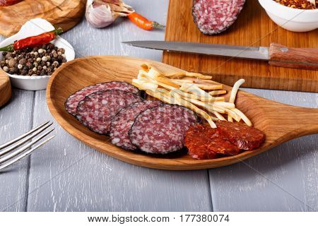 Snack set. Variety of salami and cheese chechil. Rustic style.