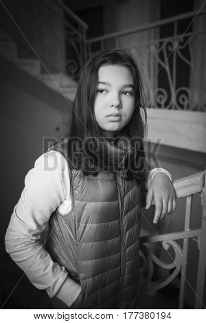 ad teenager girl at entrance of an old apartment building. black and white photo