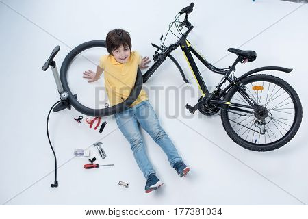 Top View Of Smiling Boy Sitting On Floor Near Bicycle On White