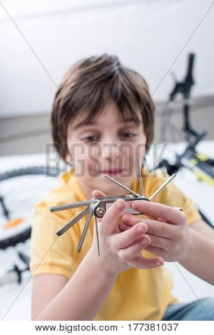 Portrait Of Little Boy Showing Bicycle Multi Tool On White