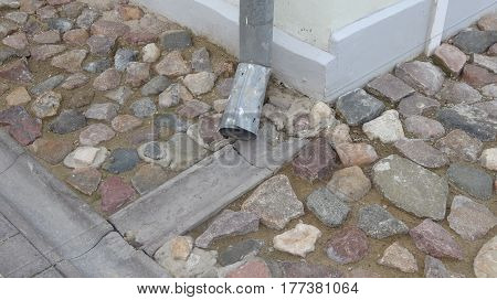 Rain water flowing from metal downspout during a flood. concept of protection against heavy downpours.