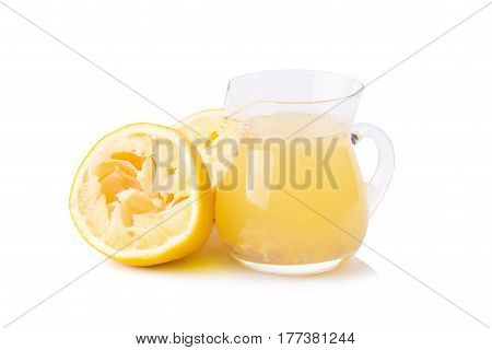 glass bowl of freshly squeezed lemon juice lemon squeezer and ripe lemons on white background.