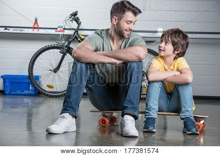 Smiling Father And Son With Folded Arms Sitting On Skateboard And Looking At Each Other