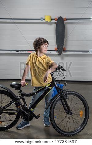 Cute Little Boy Standing With Bike And Looking Away In Workshop