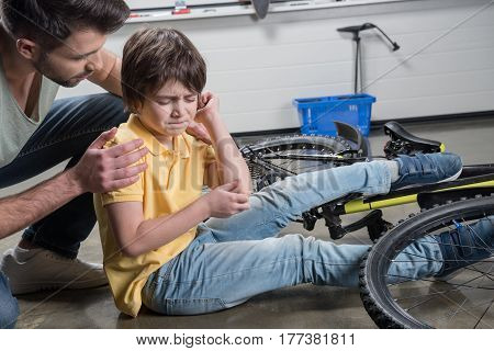Father Helping Wounded Son Getting Up From Falling Off Bicycle
