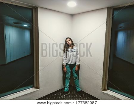 A teenage girl stands in a corner in an ominous room. mobile photo