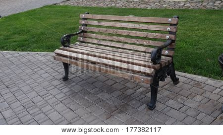 Wooden bench, with metal legs in the park on the sidewalk next to the urn.
