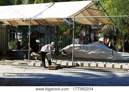 Expatriate workers laying bricks to sun dry in a cement brick laying site in AA. Mathiveri Maldives.